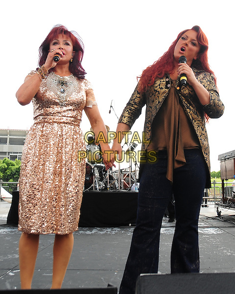 NAOMI & WYNONNA JUDD .The Judds perform at the CMA Music Festival datytime river stage, Nashville,TN, USA,.10th June 2010..country concert gig live on stage .half length band group sisters family siblings microphone holding hands gold sequined sequin beaded dress jacket  singing 3/4 .CAP/ADM/MS.©Mike Strasinger/AdMedia/Capital Pictures.