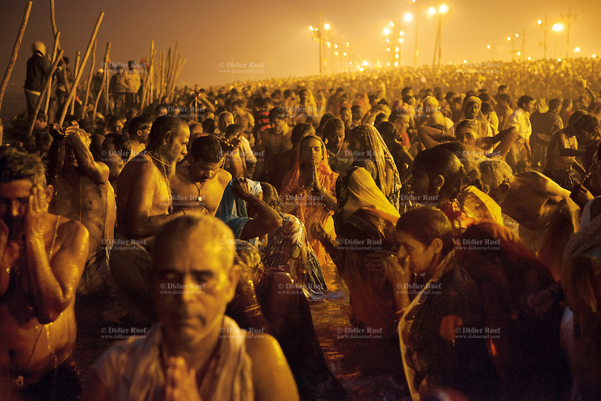 "India. Uttar Pradesh state. Allahabad. Maha Kumbh Mela. Royal bath on Basant Panchami Snan (fifth day of the new moon). The ritual ""Royal Bath"" is timed to match an auspicious planetary alignment, when believers say spiritual energy flows to earth. Indian Hindu devotees take a holy dip in Sangam at night. The Kumbh Mela, believed to be the largest religious gathering is held every 12 years on the banks of the 'Sangam'- the confluence of the holy rivers Ganga, Yamuna and the mythical Saraswati. In 2013, it is estimated that nearly 80 million devotees took a bath in the water of the holy river Ganges. The belief is that bathing and taking a holy dip will wash and free one from all the past sins, get salvation and paves the way for Moksha (meaning liberation from the cycle of Life, Death and Rebirth). Bathing in the holy waters of Ganga is believed to be most auspicious at the time of Kumbh Mela, because the water is charged with positive healing effects and enhanced with electromagnetic radiations of the Sun, Moon and Jupiter. The Maha (great) Kumbh Mela, which comes after 12 Purna Kumbh Mela, or 144 years, is always held at Allahabad. Uttar Pradesh (abbreviated U.P.) is a state located in northern India. 15.02.13 © 2013 Didier Ruef"