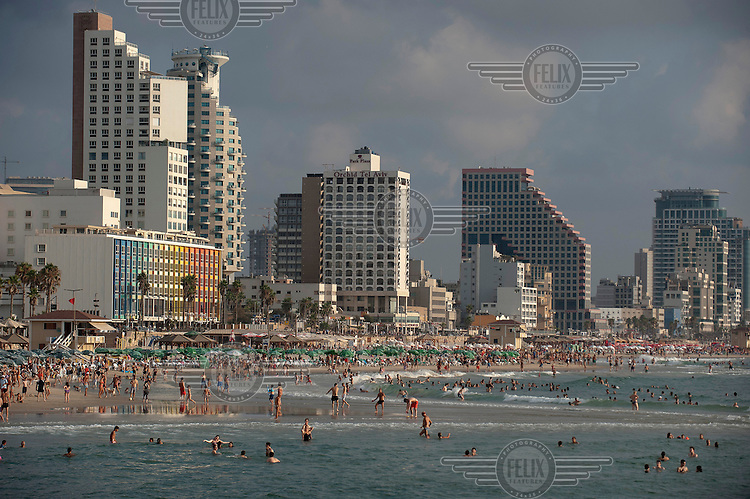 People swimming and sunbathing on the beachfront with highrise hotels behind them.