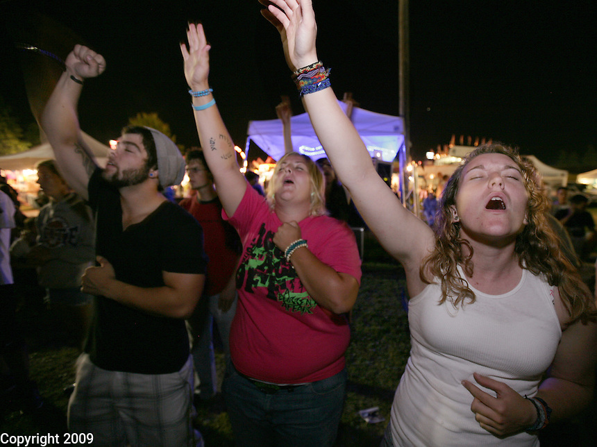 "Gregg Diacogiannis, left, Sally Jo Vander Yacht, 27, center, and Emily Faber, 20, far right, all of Lynden, rock out to the Christian band, ""Theories of Gabriela"" at the NW Washington Fair on August 19, 2009. Photo by Meryl Schenker.."