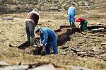 Men cutting peat on a stretch of land in the Outer Hebrides, Scotland. Peat cutting was a traditional method of gathering fuel for the winter in the sparsely-populated areas on Scotland's west coast and islands. The peat was dried and used in fires and ovens.