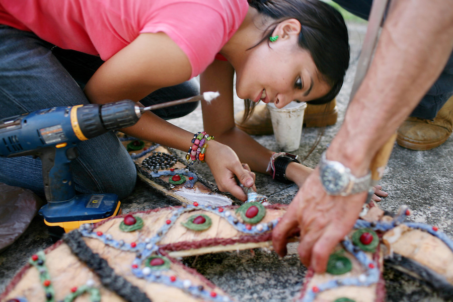 "Natalia Fernandez, 16, drills holes to assemble her costume, called  ""El Danzante del Sonido,"" the sound dancer in Spanish, at her home in Jayuya, Puerto Rico, on Tuesday, November 18, 2008. Her costume will weigh about 35-lbs and she will wear it for three hours in a parade around the plaza in Jayuya. Residents celebrate the 39th annual Festival Indigena de Jayuya, which honors their Taino Indian heritage."