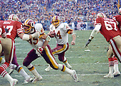 Washington, D.C. - January 8, 1984 -- Washington Redskins running back John Riggins (44) carries the ball in the NFC Championship game against the San Francisco 49ers at RFK Stadium in Washington, D.C. on Sunday, January 8, 1984.  Defending on the play are San Francisco 49ers Dan Bunz (57) and nose tackle Pete Kugler (67).  Redskins tight end Don Warren (85) blocks for Riggins.  The Redskins won the game 24 - 21 to advance to Super Bowl XVIII.  <br /> Credit: Howard L. Sachs / CNP