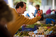 A man buys tomatoes in an outdoor market in Italy.