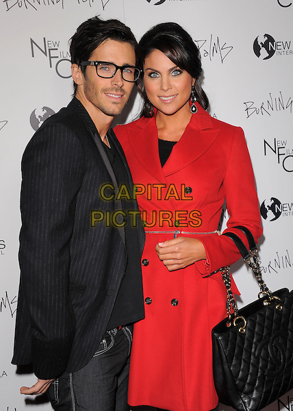 "BRANDON BEEMER & NADIA BJORLIN .attending the New Films Cinema's Premiere of ""Burning Palms"" held at The Arclight Theatre in Hollywood, California, USA, January 12th 2011..half length black  red coat bag belt silver jacket pinstripe geek glasses  .CAP/RKE/DVS.©DVS/RockinExposures/Capital Pictures."