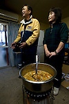Mitsuo Sugawara and his wife Tomoko stand by a pot of miso and vegetable broth at their farm in Higashi-Matsushima, Miyagi Prefecture, Japan on 30 Nov. 2011.Photographer: Robert Gilhooly