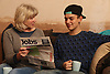 Teenager with grandmother looking at newspaper for jobs