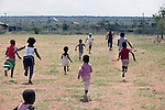 GA-MASEHLONG, SOUTH AFRICA -  MARCH 28: Children run on a soccer field where Caster Semenya learned how to run on March 28, 2010, in Ga-Masehlong, South Africa. Caster Semenya, age 19, a runner who won the 800 meters world cup title in Berlin, Germany in 2009. She was later gender tested as she blew away the competition. She has not competed in any race since then but she is still a role model for relatives and children in the rural poor village. She was raised in the on the right and the newly constructed house is a gift from the local government. (Photo by Per-Anders Pettersson/Getty Images