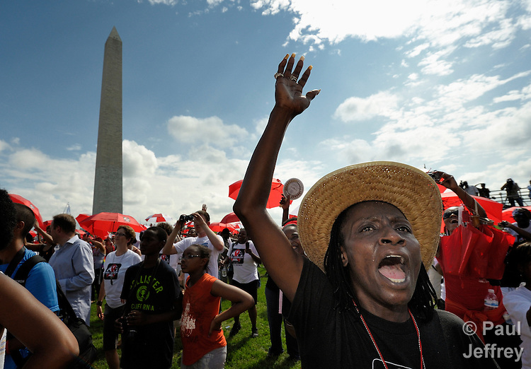 With the Washington Monument in the background, participants in a July 22, 2012, march and rally in Washington, DC, demand that the U.S. and other governments keep their promises to fund global relief programs for those living with HIV and AIDS. The march took place as more than 23,000 delegates gathered in the city for the XIX International AIDS Conference.