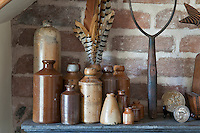 A detail highlighting a collection of antique rustic bottles displayed on the living room mantelpiece