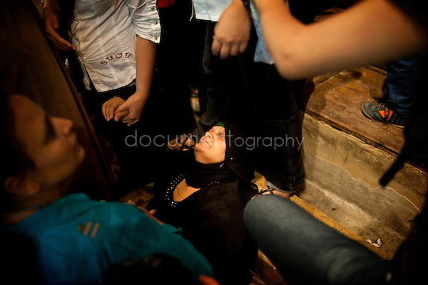 A woman loosing consciousness while Father Samaan approaches to her. <br />