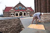 Robert Jennings fastens temporary ramps across uneven concrete walkways in front of St. Paul Catholic Church in Westerville,OH, as construction nears completion before the start of winter.