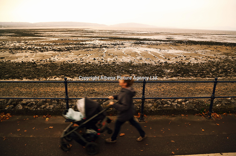 """Pictured: A woman walks with a pushchair at the seaside village of Mumbles near Swansea, UK. Monday 16 October 2017<br />Re: Remnants of Hurricane Ophelia are expected to bring strong gusts of wind to Wales when it hits Britain's shores.<br />The hurricane, making its way from the Azores in the Atlantic Ocean, will have weakened to a storm when it arrives.<br />A Met Office amber """"be prepared"""" warning has been issued in some areas bringing """"potential danger to life""""."""