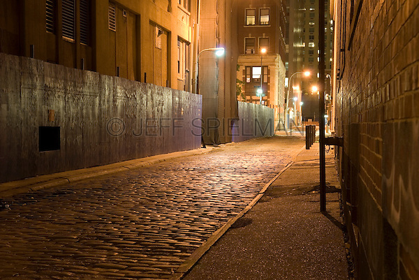 AVAILABLE FROM JEFF AS A FINE ART PRINT.<br /> <br /> AVAILABLE FROM PLAINPICTURE FOR COMMERCIAL AND EDITORIAL LICENSING.  Please go to www.plainpicture.com and search for image # p5690005.<br /> <br /> Dark Alley with Cobblestones, Illuminated at Night, Lower Manhattan, New York City, New York State, USA