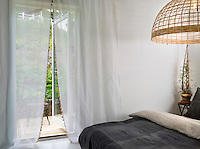 Double doors behind sheer curtains in the guest room open out onto a private terrace. The sheets, cushions and bedpread are by Jimmy Schoenning Hem