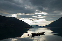 row boat sits moored near shore of  Innviksfjorden with reflection of distant mountains, near Olden, Norway