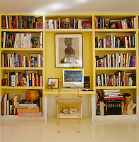 The living room wall is lined with floor-to-ceiling purpose-built bookcases and a desk