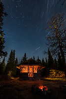 Star trails above a log cabin.