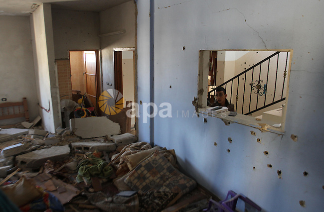 Palestinians look in a house filled with debris where Palestinian Hamas militant Hamza Abu Alhija was killed in the West Bank refugee camp of Jenin March 22, 2014. Israeli forces shot and killed four Palestinians on Saturday during a raid on the home in the occupied West Bank to capture Alhija, a wanted Hamas Islamist militant, the Israeli military said. Hamas supporters carried three bodies through the streets of the West Bank city of Jenin, shouting slogans against Palestinian President Mahmoud Abbas, involved in U.S.-brokered peace talks with Israel. Photo by Nedal Eshtayah