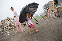 """A small child holds an umbrella in a junk yard where migrant workers pick apart electronic trash in Nanyang. Each year, between 20 and 50 million tons of electronic waste is generated globally. Most of it winds up in the developing world.Some of the most popular destinations for dumping computer hardware include China, India, and Nigeria. It can be 10 times cheaper for a """"recycler"""" to ship waste to China than to dispose of it properly at home. With the market for e-waste expected to top $11 billion by 2009, it's lucrative to dump on the developing world."""