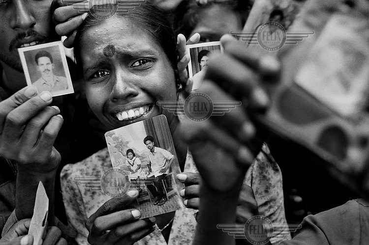 Tamil internally displaced persons (IDPs) hold up photographs of male relatives who were abducted by Sri Lankan security forces after a raid on their camp. The war in Sri Lanka between the Sinhalese dominated government and the Tamil Tiger rebels has resulted in tens of thousands of deaths. Thousands more have disappeared.