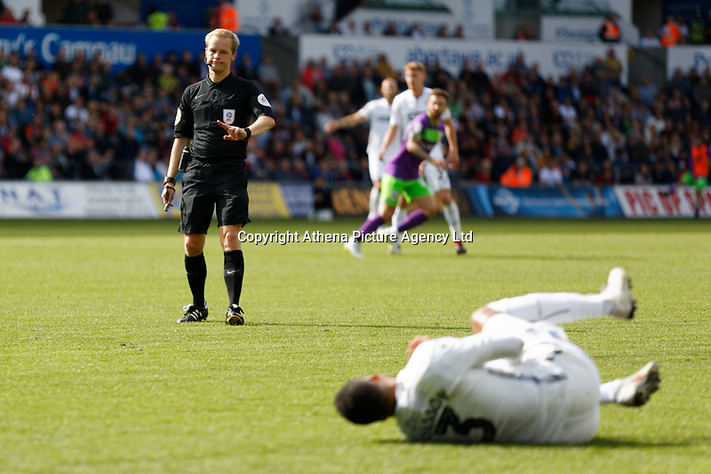 Referee Gavin Ward refuses to award a foul to Martin Olsson of Swansea City who rolls on the ground (R) during the Sky Bet Championship match between Swansea City and Bristol City at the Liberty Stadium, Swansea, Wales, UK. Saturday 25 August 2018
