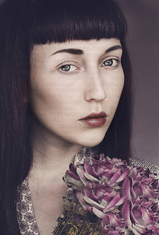 Young female with pale skin, blue eyes and dark hair, holding purple flowers, looking with a sad expression at the camera.