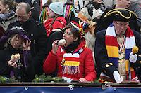 Ministerpräsidentin Malu Dreyer beißt in einen Kreppel aus dem Geschenkkorb des CCW - Rosenmontagsumzug in Mainz