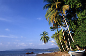 Marenco, Osa Peninsula, Costa Rica. Unspoilt palm fringed beach with freshly painted blue and white open boat.