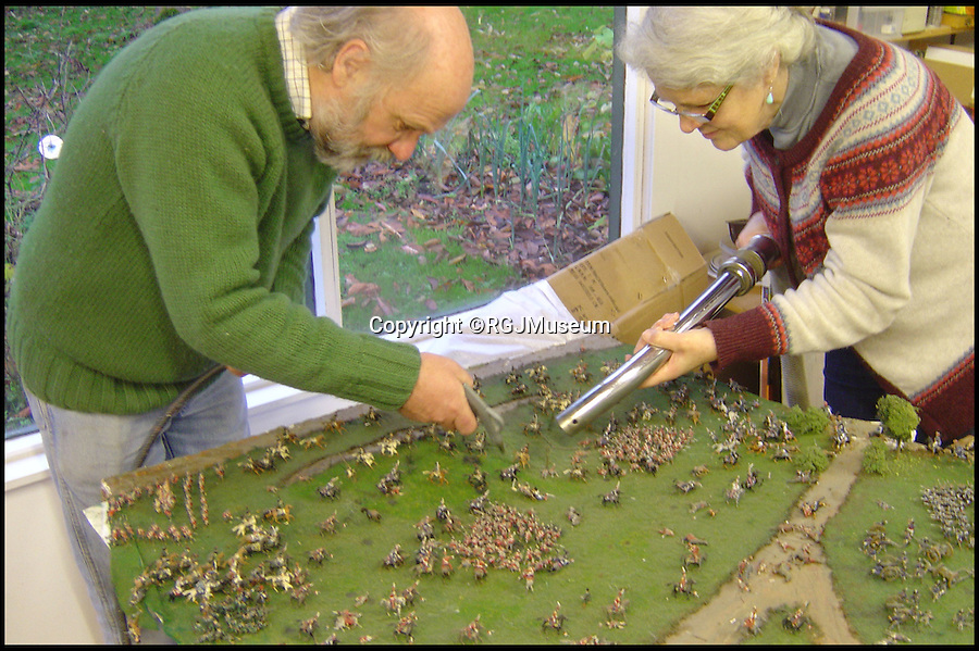 BNPS.co.uk (01202 558833)<br /> Pic: RGJMuseum/BNPS<br /> <br /> The Thatchers delicately hoovering the tiny figures.<br /> <br /> Historic battle brought back to life...<br /> <br /> A stunning diorama of the battle of Waterloo has been restored to its former glory after a painstaking cleaning operation to remove nearly 50 years of dust.<br /> <br /> The sweeping panorama contain's 21,500 figures and nearly 10,000 horses, each of which has been meticulously cleaned by hand over the last five months by husband and wife team Kelvin and Mary Thatcher from Norfolk.<br /> <br /> The pristine model has now gone back on display at the refurbished Royal Green jackets museum in Winchester.<br /> <br /> A sobering fact is that there were over twice as many casualties in the actual battle as there are figures on the diorama.