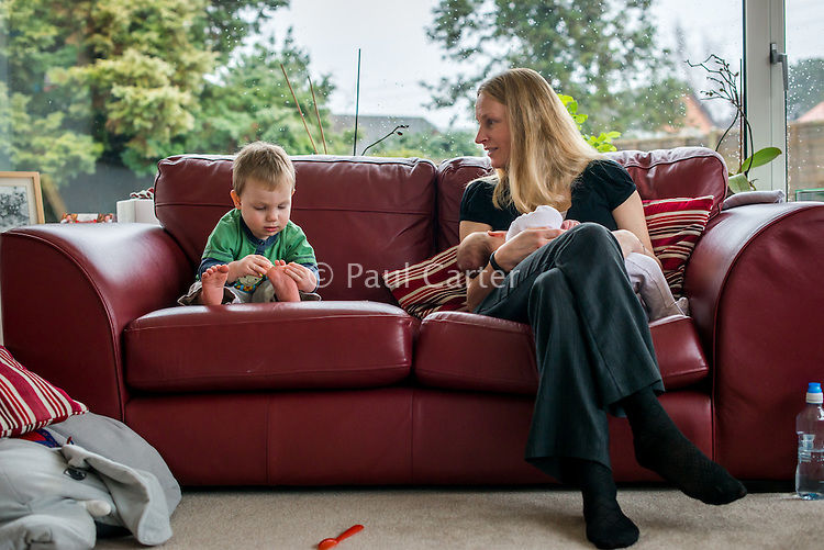 A woman sitting on a sofa breastfeeding her 2 month old baby while interacting with one of her older sons who is examining his foot.<br /> <br /> Hampshire, England, UK<br /> 10/02/2013