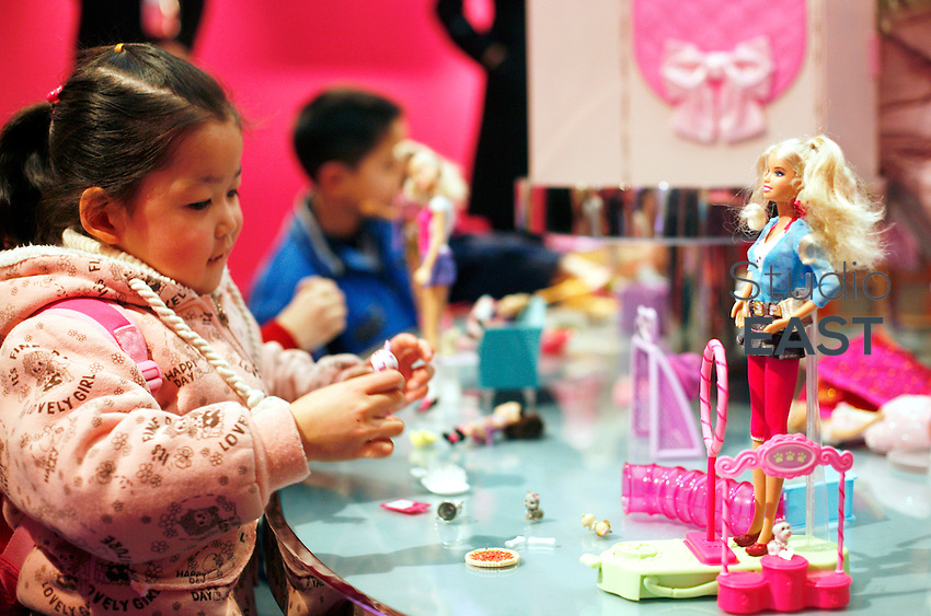 A little girl plays with Barbie accessories, in Barbie giant store in Shanghai, China, on March 6, 2009. Shanghai now boasts the world's biggest Barbie store after its six-storey pink palace opened on March 6. The $A44 million store's opening coincides with Barbie's 50th birthday. The doll's makers, Mattel, insist it will capture the imagination not just of young girls but of Chinese women of all ages, with more than 1600 products for sale. For younger girls, the store offers a catwalk on which they can model Barbie-esque clothes and assistants to teach them how to sing and dance to the Barbie Girl song. The Shanghai store is a crucial step in Mattels efforts to make China the number one market for Barbie dolls, while Chinese sales currently account for about 2.5 per cent of global sales. Photo by Francois Dorleans/Pictobank