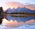 USA; Wyoming, Grand Teton National Park.   Grand Tetons reflecting in the Snake River at Sunset