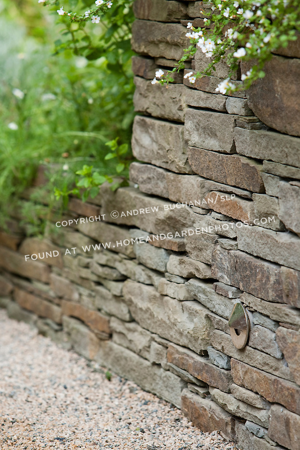 Perennials cascade down stacked stone walls that edge the stone path in a Seattle backyard.