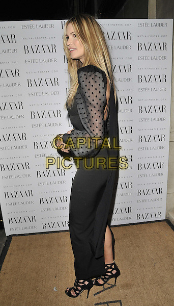 Elle Macpherson.The Harper's Bazaar Women Of The Year Awards, Claridge's hotel, Brook St., London, England..November 7th, 2011.full length black dress belt strappy sandals gold clutch bag polka dot sleeves sheer side.CAP/CAN.©Can Nguyen/Capital Pictures.