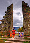 A local worshipper carries supplies into the Hindu temple of Ulun Danu at Candikuning (on Bali, Indonesia) for a ceremony today.  Located in the high hills of the Bedugul, about 30 miles north of Bali's capital city of Denpasar, the temple is built on the shores of the crater Lake Bratan (formed from the sunken crater of a long-dormant volcano).  Much of the inner precincts of the temple is closed to the (non-Hindu) public, but the gardens are spectacular and feature fabulous shrines, statuary, and views. (HDR image)