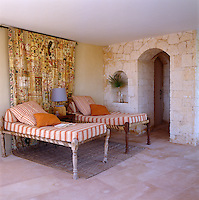 Wooden beds with bright striped mattresses and a tapestry on the wall behind are from India