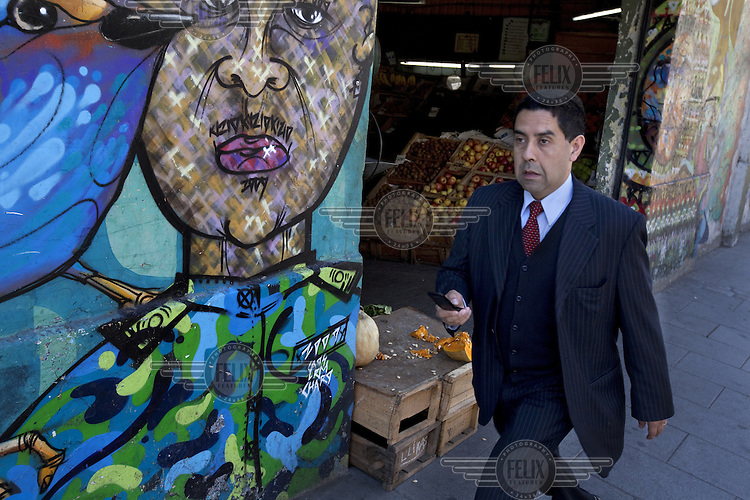 A business man checks his mobile phone as he walks past a fruit market, it's walls covered in graffiti by artists, Charquipunk, La Robot de Madera and Caos...