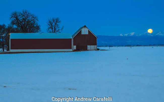 An old barn makes for a nice foreground as a full moon sets behind the Rocky Mountains in Northern Colorado.