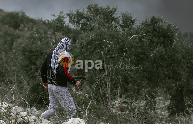 A Palestinian protester hurls a stone towards Israeli security forces during clashes following a weekly demonstration against the expropriation of Palestinian land by Israel in the village of Kfar Qaddum, near the West Bank city of Nablus on January 17, 2020. Photo by Shadi Jarar'ah