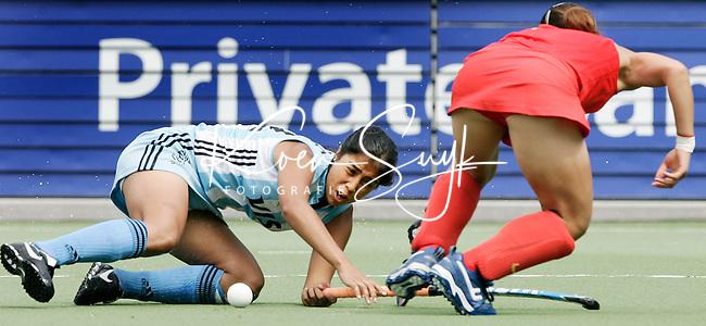 AMSTELVEEN - De Argentijnse Mariana Gonzalez Oliva wordt gestopt door de Chinese Yan Shao Mai, zondag tijdens de wedstrijd Arentinie-China (1-3) om de Rabo Champions Trophy 2006 in Amstelveen. ANP PHOTO KOEN SUYK