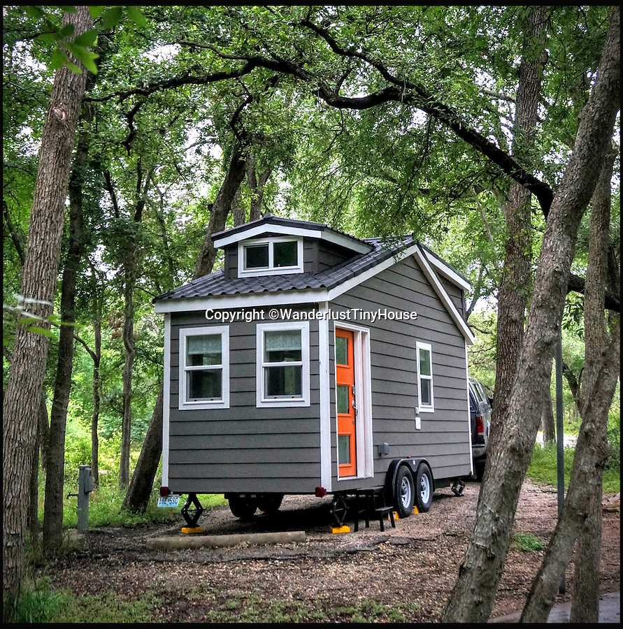 BNPS.co.uk (01202 558833)<br /> Pic: WanderlustTinyHouse/BNPS<br /> <br /> Cottage in the woods - McKinney Falls State park.<br /> <br /> Wanderlust for homebird's -  a young couple have solved the problem of leaving a much loved home to go travelling, by strapping a downsized version to the back of their pick-up and taking it with them.<br /> <br /> Patrick Howard and Lauren Kennedy ditched their office jobs, sold most of their worldly possessions and their 2,000 sq ft home and bought the miniscule 200 sq ft house, which can be towed by a pick-up truck.<br /> <br /> The pair, who were both electrical engineers, are now on their trip of a lifetime travelling all over the United States with their two dogs, Otis and Colbie.<br /> <br /> They are part of the Tiny House Movement - a growing group of people who are buying small houses and enjoying simpler lives.