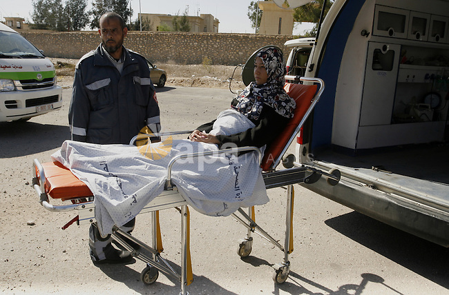 A Patient lies on a bed outside an ambulance at the Rafah border crossing in the southern Gaza Strip on November 6, 2014. Egypt closed the crossing into the Gaza Strip, the only route into the Palestinian territory not controlled by Israel, after Egyptian president Abdel Fattah al-Sisi declared a state of emergency on October 25, 2014, for three months, after the death of 30 soldiers in a suicide attack. Photo by Abed Rahim Khatib