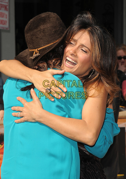Constance Marie and Salma Hayek .The L.A. Premiere of 'Puss in Boots' held at The Regency Village  Theatre in Westwood, California, USA..October 23rd, 2011 .half length dress hands arms hug embrace back behind top blue turquoise hat smiling mouth open brown one shoulder dress funny.CAP/RKE/DVS.©DVS/RockinExposures/Capital Pictures.