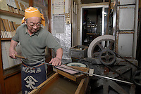 3rd generation knife shop owner Azuma Masahisa sharpening a tuna knife in his shop.