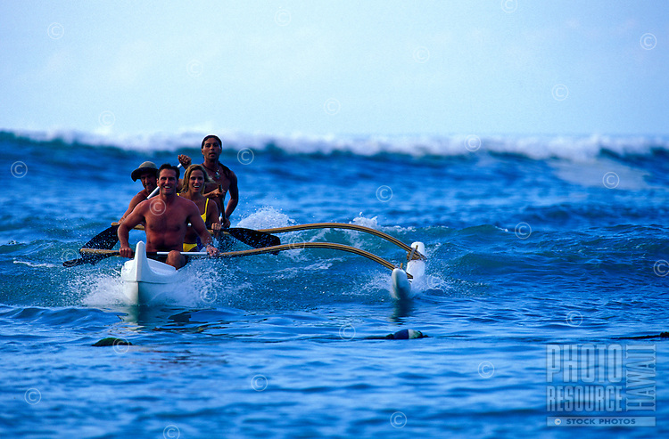 Four friends paddling an outrigger canoe through the waves