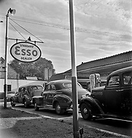 Morning of July 21st, the last day before stricter gas rationing went into effect, cars were parked in front of gas stations long before they opened, waiting to fill their tanks on the quota. Washington, DC 1942.
