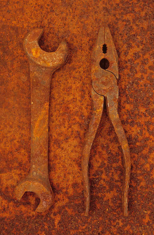 Rusty old double-headed spanner lying next to rusty pliers on rusty metal sheet