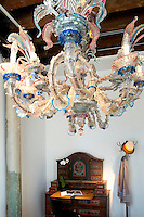 Antique painted wood desk and colorful chandelier