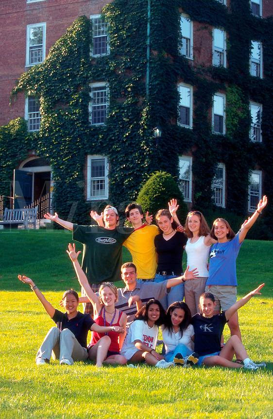 Group of college students posing on campus lawn.